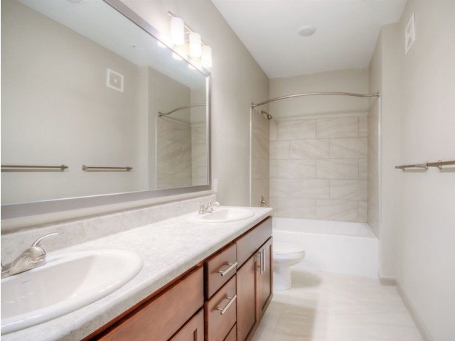 San Mateo Apartments Kissimmee Florida bathroom with double sink vanity, expansive mirror, dual lights, tub/shower combo with tile floors and tub walls