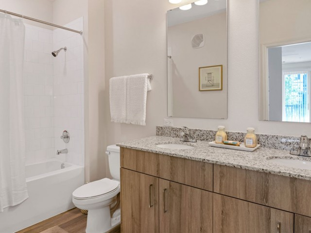 Venetian Apartments Ft. Myers bathroom with tub/shower and double sink with granite, double mirrors and expansive cabinets