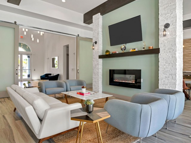 Venetian Apartments Ft. Myers lounge area with television and fireplace