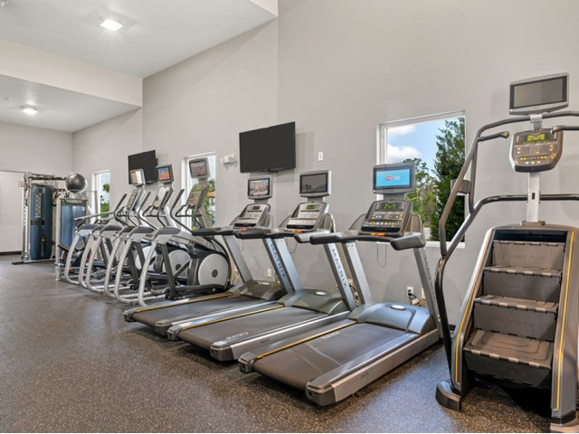 Venetian Apartments Ft. Myers fitness center with multiple cardio equipment pieces including stair stepper, treadmill, and elliptical machine