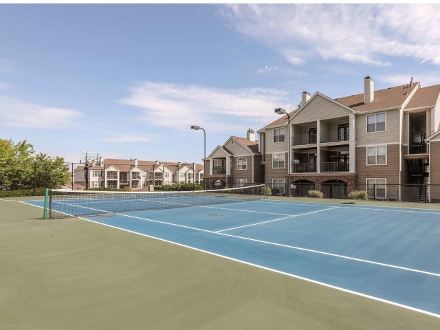 tennis court with apartments behind