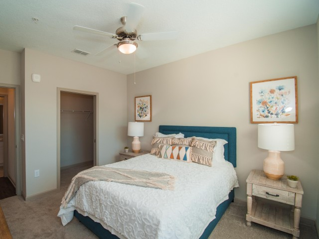 Tomoka Pointe Apartments Daytona Beach Florida furnished guest bedroom , carpeted floor, ceiling fan with light, adjacent walk in closet