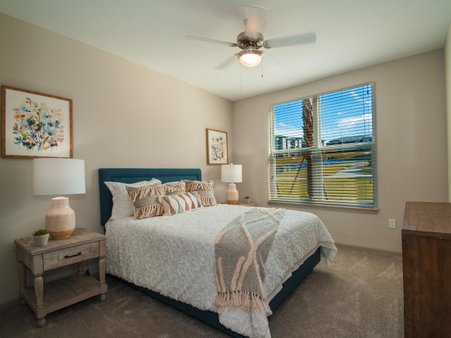 Tomoka Pointe Apartments Daytona Beach Florida furnished model guest bedroom with ceiling fan with light fixture, double window with blinds, carpeted flooring