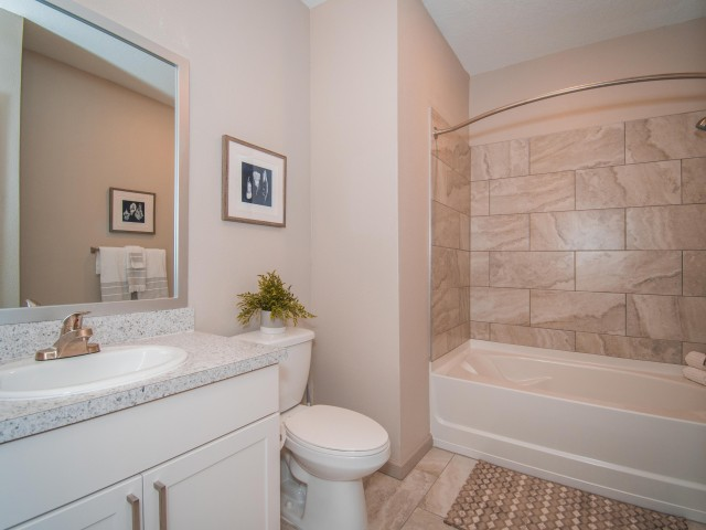 Tomoka Pointe Apartments Daytona Beach Florida guest bathroom with single sink, shaker style cabinet with stainless steel handles, framed mirror, tub/shower combo with tile walls, curved rod, tile flooring