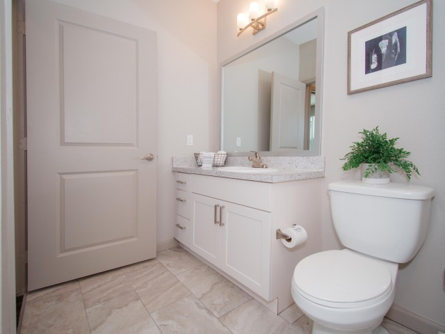 Tomoka Pointe Apartments Daytona Beach Florida guest bath tile flooring, single sink with shaker cabinets with drawers, framed mirror, modern light sconce, toilet