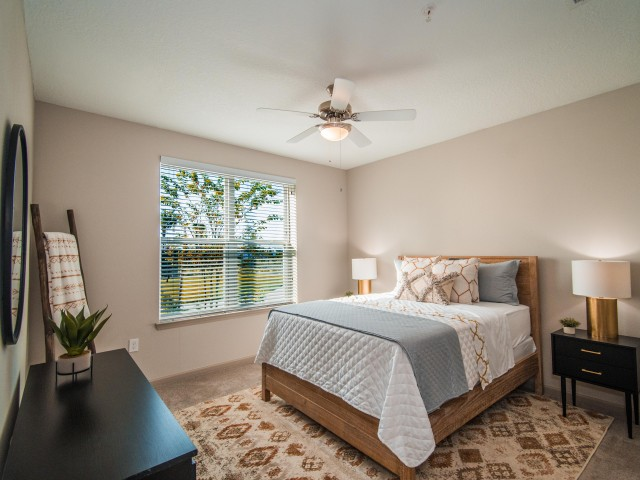 Tomoka Pointe Apartments Daytona Beach Florida furnished model bedroom with ceiling fan with light, double window with blinds, carpeted flooring