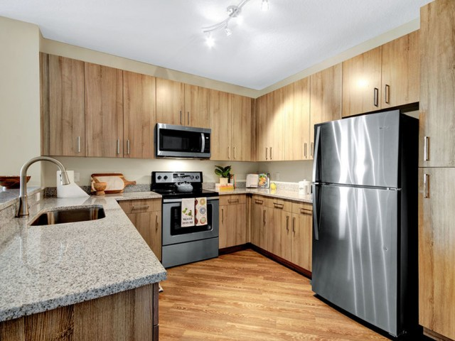 400 north apartments Maitland Florida kitchen with stainless appliances, wood cabinets and flooring and granite counters