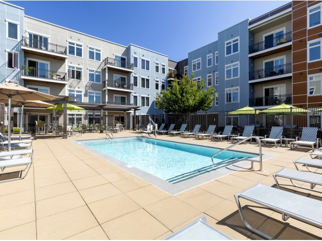 Rectangular pool with lounge chairs and umbrellas surrounding. Apartment building encircles pool deck.