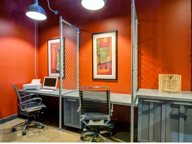 Industrial style business center with red walls and exposed white brick. Two computer monitors on counters with rollings chairs separated by chain link partitions. Printer and fax sit on adjacent counter with cabinet storage underneath larg