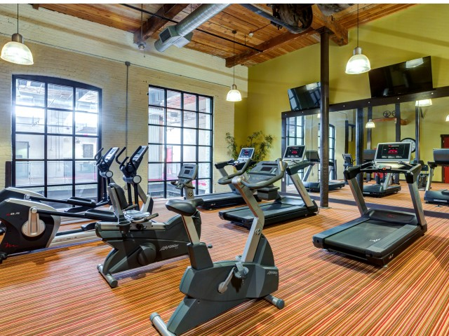 View of carpeted fitness center with exposed beam ceiling, treadmills, ellipticals, stationary bikes and circuit training equipment arranged throughout room