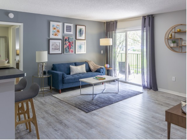 Model, furnished living room with balcony, couch, two end tables, coffee table, decor, and hardwood flooring