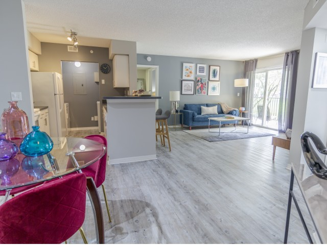 Furnished model with open concept kitchen, living, and dining room with hardwood flooring