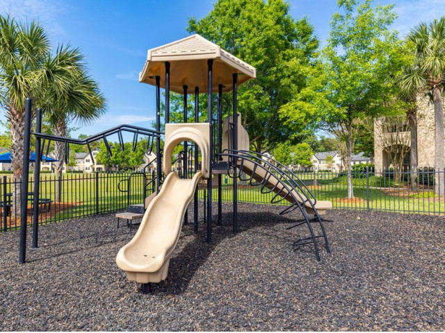 Park Lane Apartments in Gainesville fenced playground with mulch, monkey bards, slide and shading