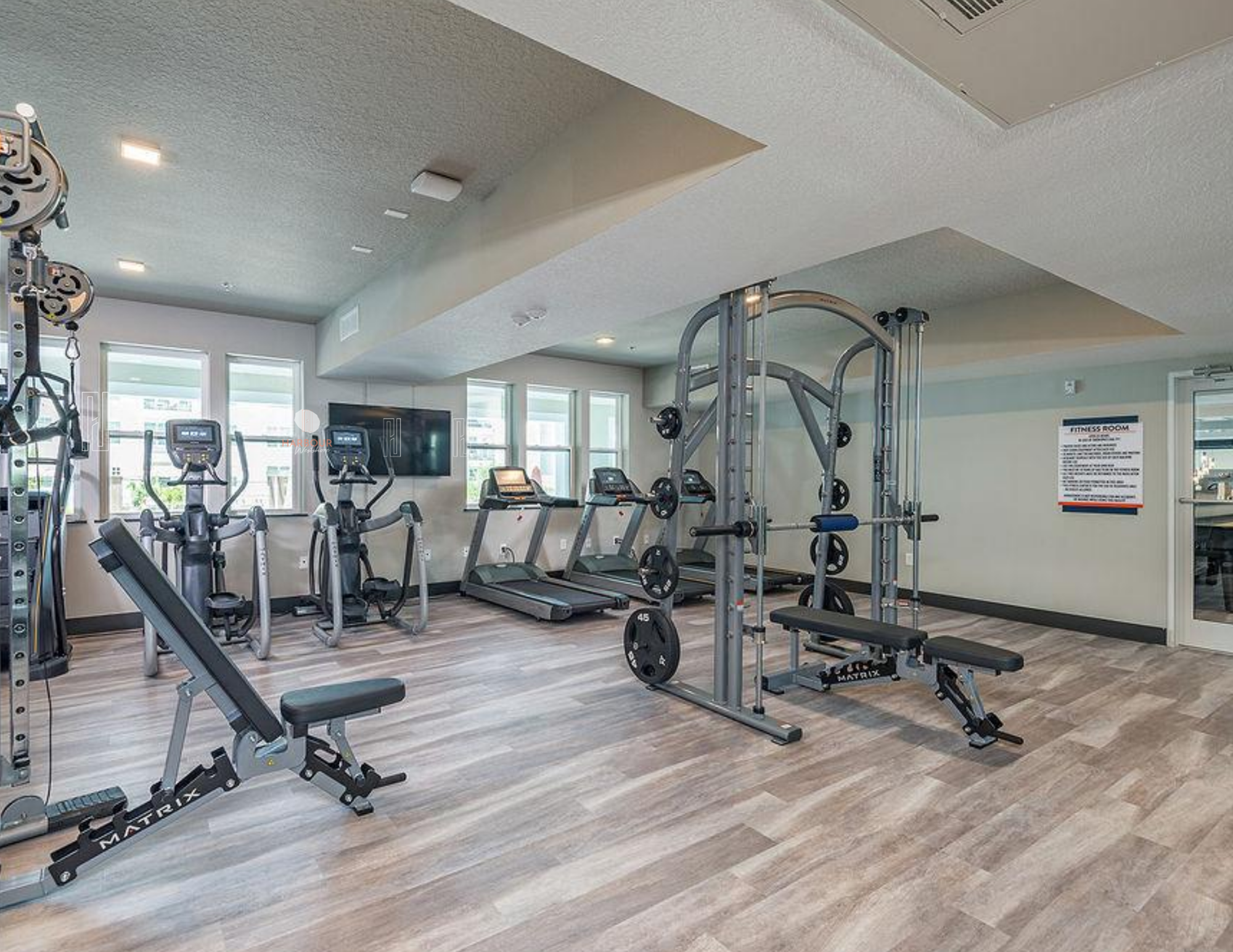 fitness center with strength and cardio equipment, television on wall, plank flooring