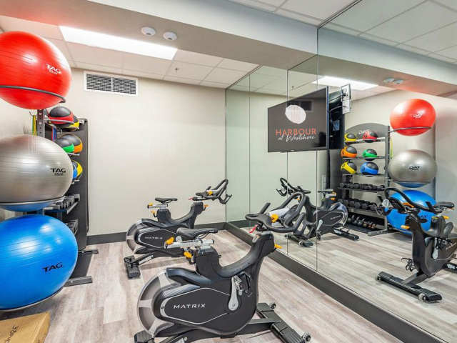 yoga and spin room with spin bikes, tv on wall for fitness on demand, pilates equipment