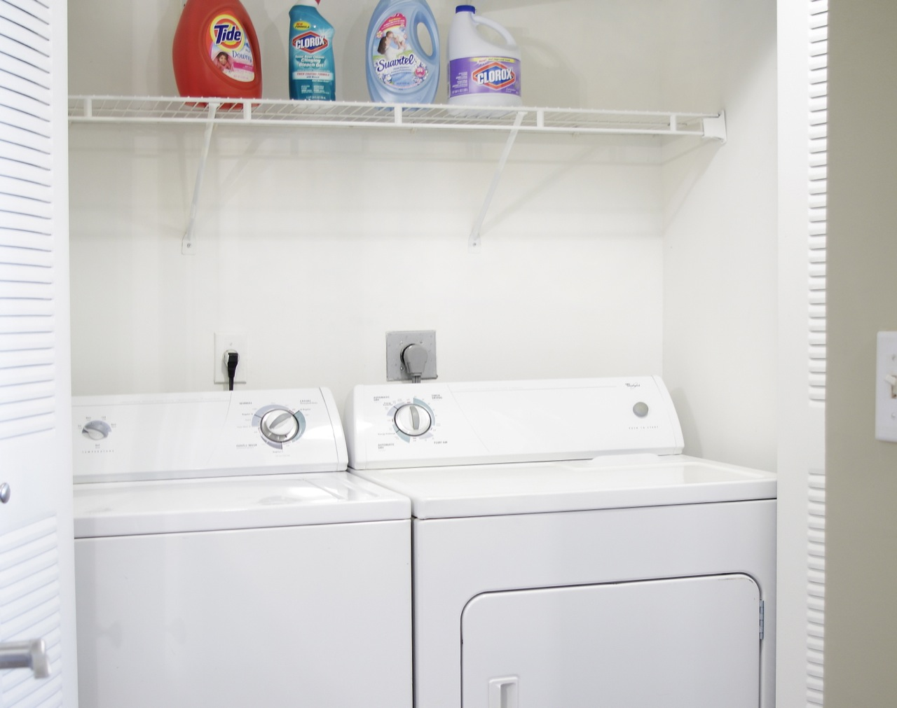 In-unit washer and dryer machines located inside of double-door closet. Overhead wire shelving holding laundry detergents