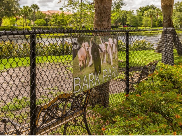 Dog Park sign on chain link fence with trees, pond, and grassy area