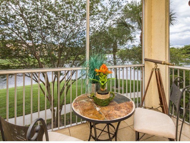 Screened patio with table and two seats overlooking lawn area and pond