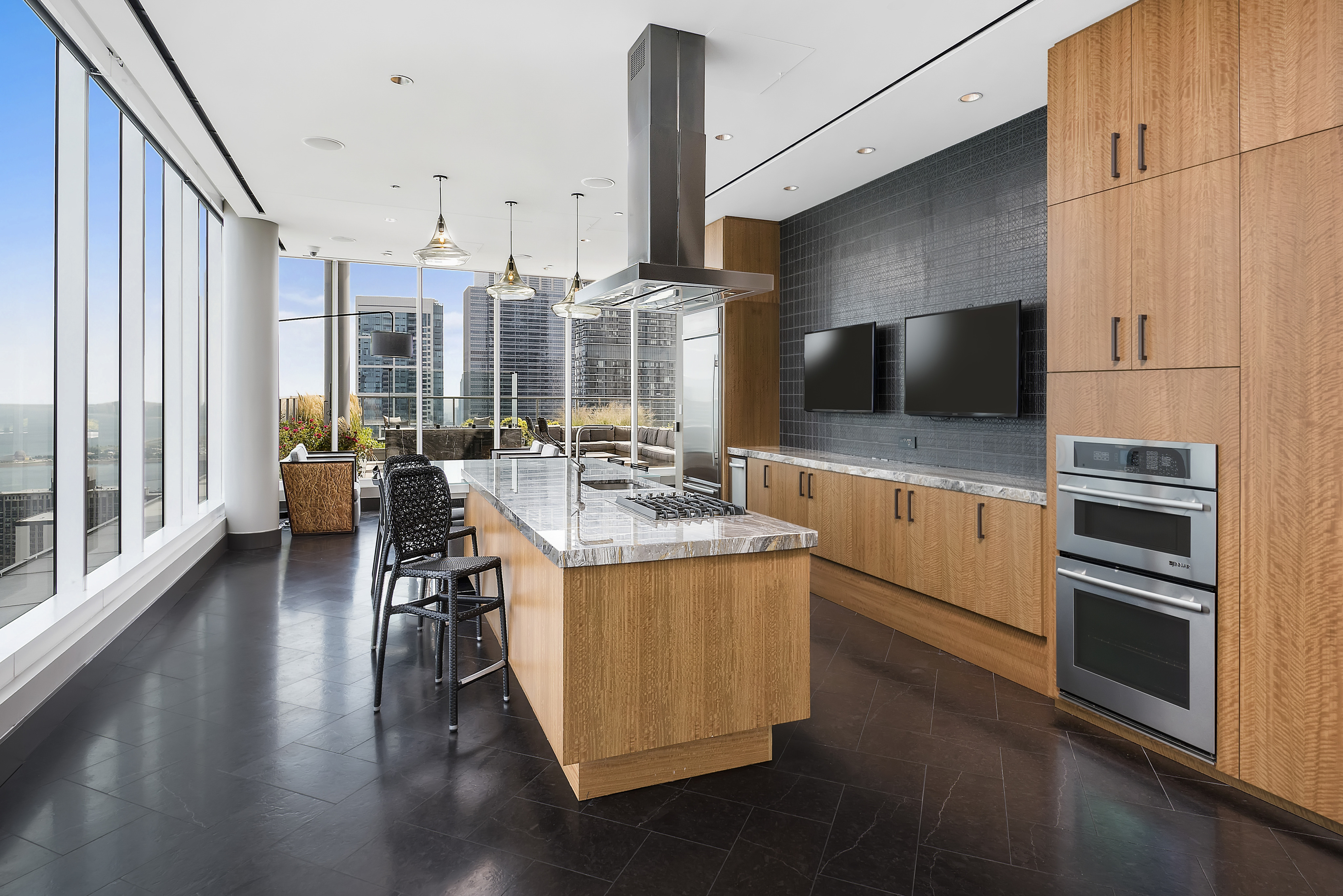 Rooftop sky lounge with a catering kitchen, flat-screen TVs, an island and floor-to-ceiling windows with a city view