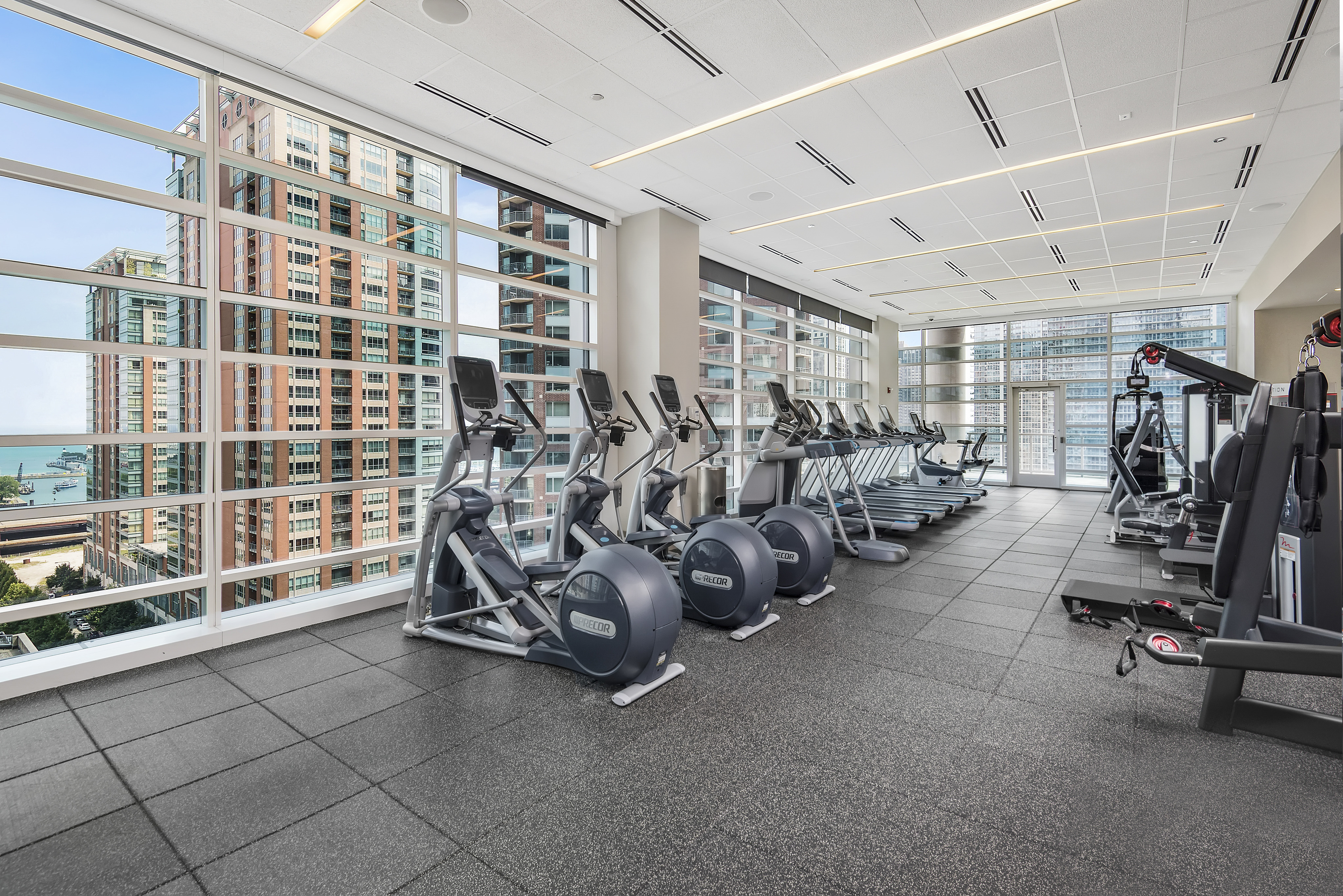 Fitness center with exercise equipment, floor-to-ceiling windows and city views