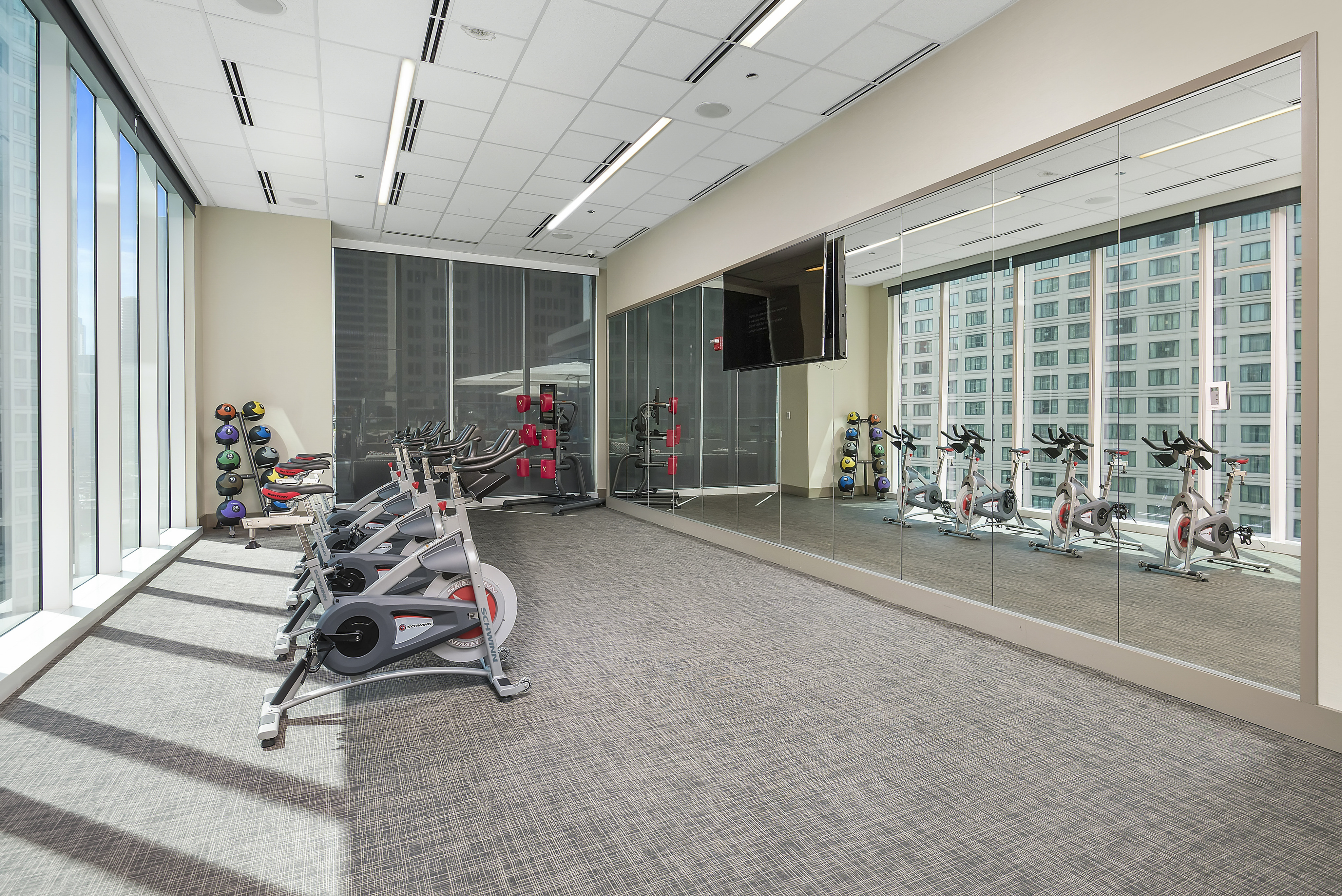 Fitness center with stationary bikes, mirrors and a flat-screen TV