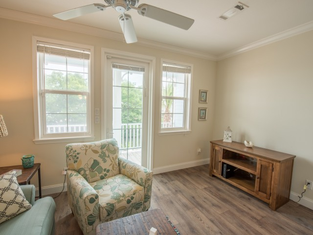 Furnished sitting area with ceiling fan in resident lounge facing back porch