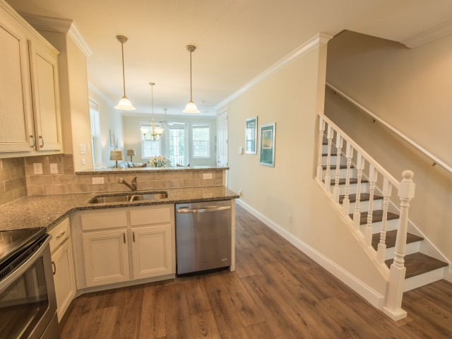 Kitchen with sink, stainless steel oven and dishwasher next to stairs