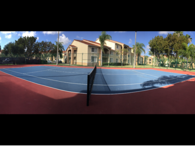 Panoramic view of community outdoor tennis court, fenced on all sides