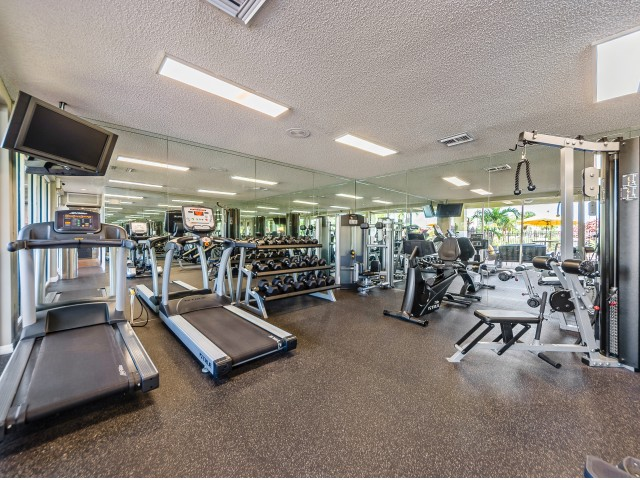 Fitness center with treadmills, stationary bicycle, weight machines, and free weights