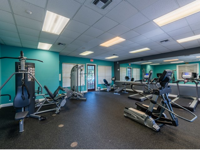 Fitness center with mirrored wall, treadmills, workout benches, and various weight machines