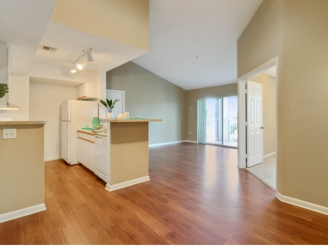 Apartment kitchen with white refrigerator and dishwasher connected to unfurnished living room with wood floors, vaulted ceiling, tracking lighting, sliding glass balcony doors, and raised bar peninsula countertop