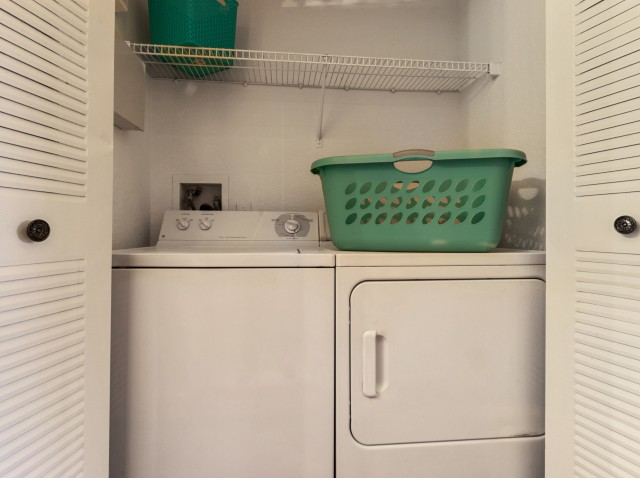 Apartment laundry room with a top loading washer, side loading dryer, and shelving above