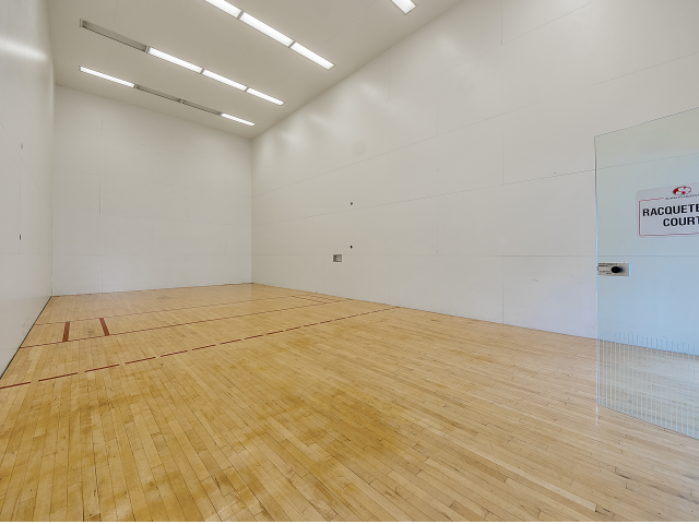 Large indoor community racquetball court with wood flooring and glass door entry