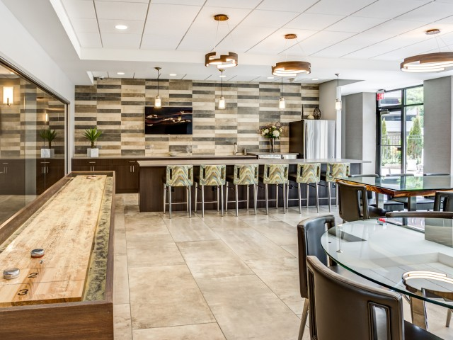 Modern club room with comfortable seating options and a shuffleboard