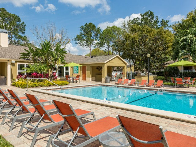 swimming pool with orange lawn chairs