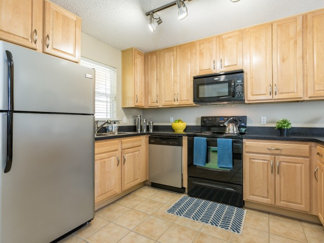 kitchen with light brown cabinets, black stovemicrowave and stainless refrigerator