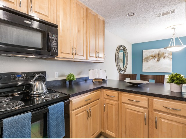 kitchen with black microwave above black stove, dark countertops and many cabinets