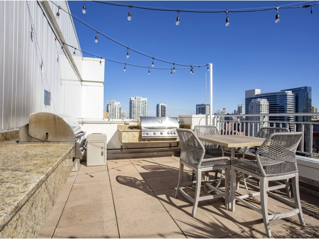Rooftop grilling station with city views and dining area