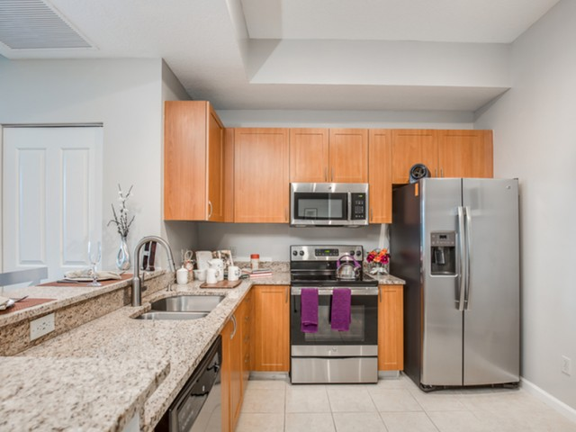 The Strand View of kitchen with wood tone cabinets, light granite countertops and stainless steel appliances