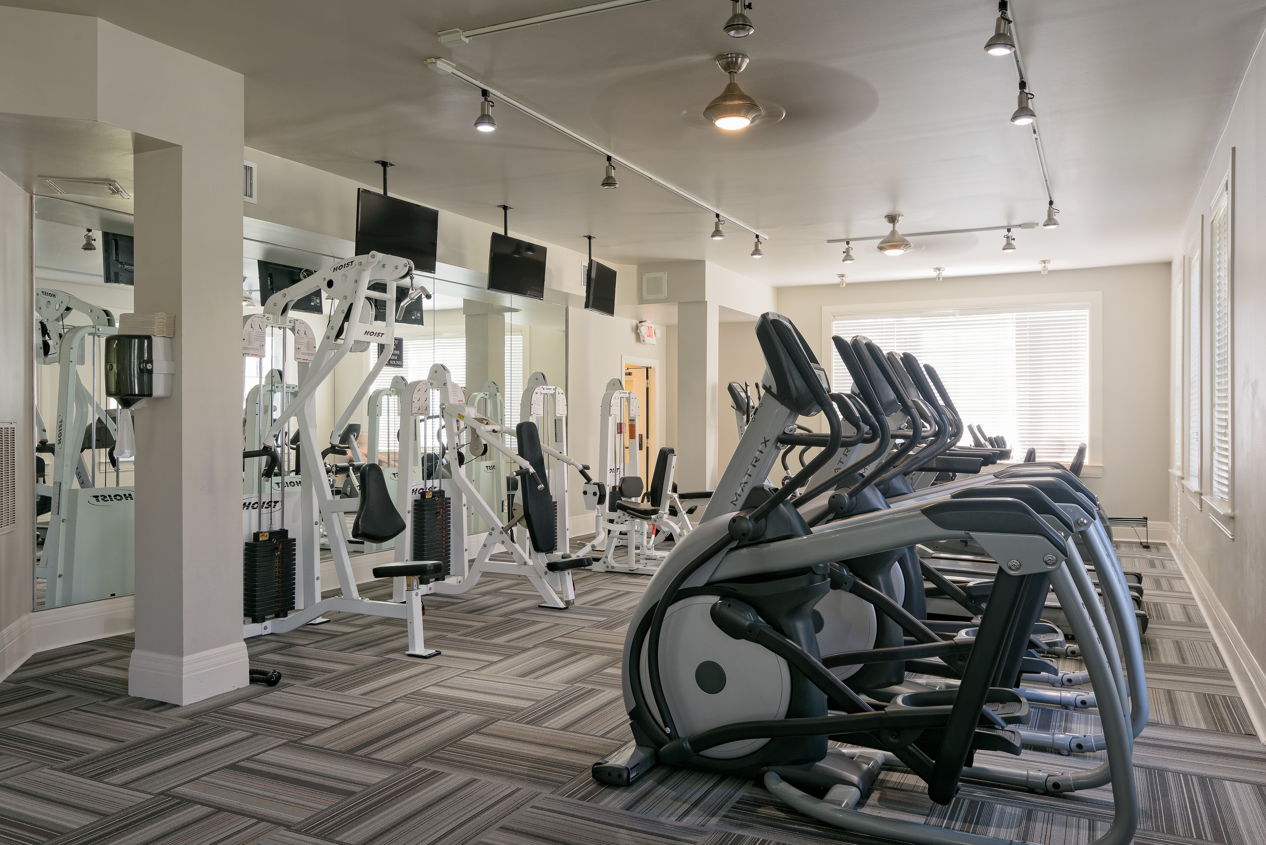 Fitness center with weight machines, wall TVs, pendant lights, and cardio equipment