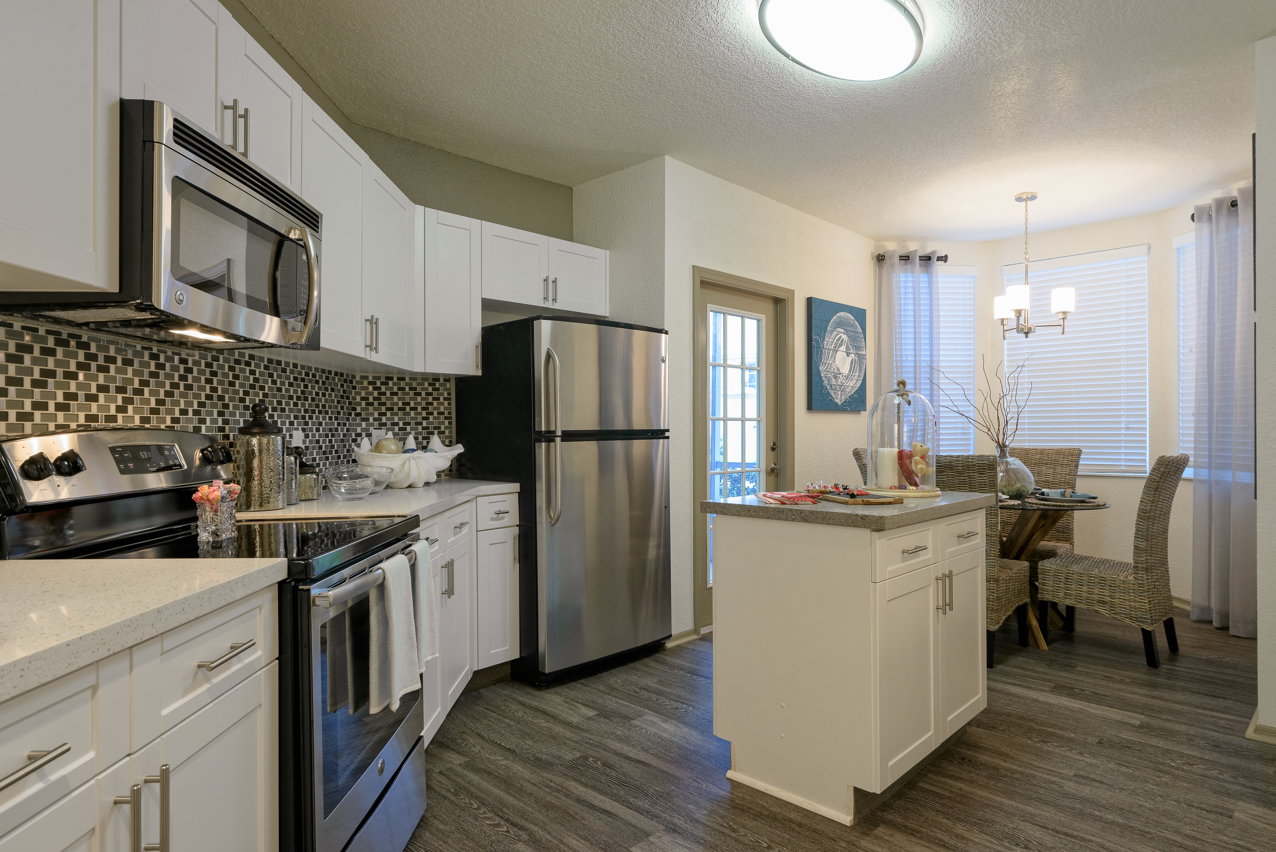 Apartment kitchen with wood like flooring, small island, tiled backsplash, stainless steel appliances, patio door and breakfast nook with windows