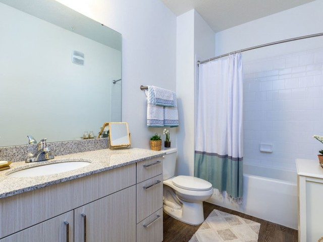 m2 at millenia bathroom with tub-shower combo, tile surround, light wood cabinets and undercounted sink