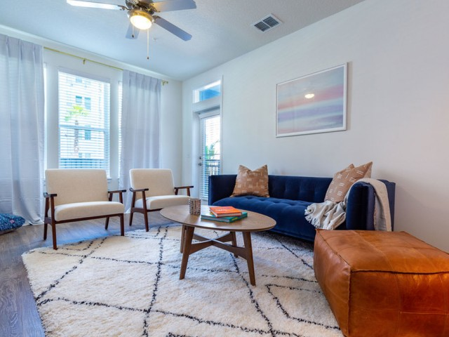 m2 at millenia living room with French door to patio, triple window and ceiling fan with lighting