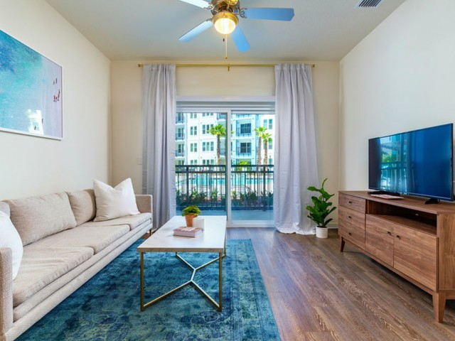 m2 at millenia living room with patio door, ceiling fan with light and wood vinyl flooring
