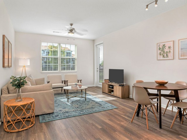 Venetian Apartments in Ft. Myers living room with wood plank flooring and ceiling fan with light