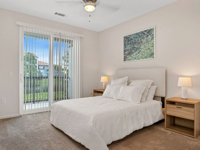 Venetian Apartments in Ft. Myers bedroom with sliding door to patio, carpet on floors and a ceiling fan with light
