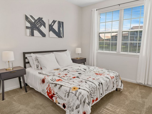 Venetian Apartments Ft. Myers guest bedroom with queen size bed and end tables, plush carpet and double window.