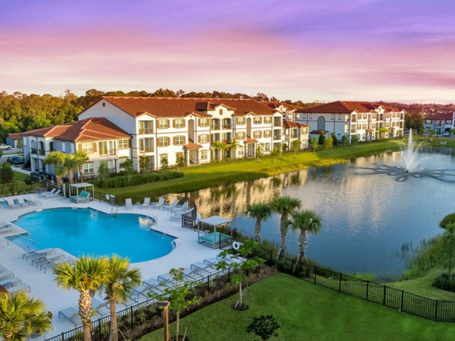 Venetian Apartments Ft Myers aerial shot of pool deck next to lake with fountain and buildings in the back at sunset