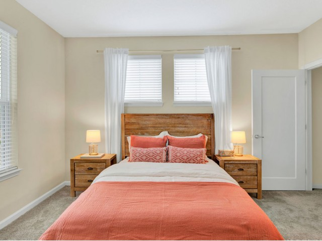 400 north apartments Maitland Florida bedroom with queen bed and two end tables, three windows and walk in closet with plush carpet