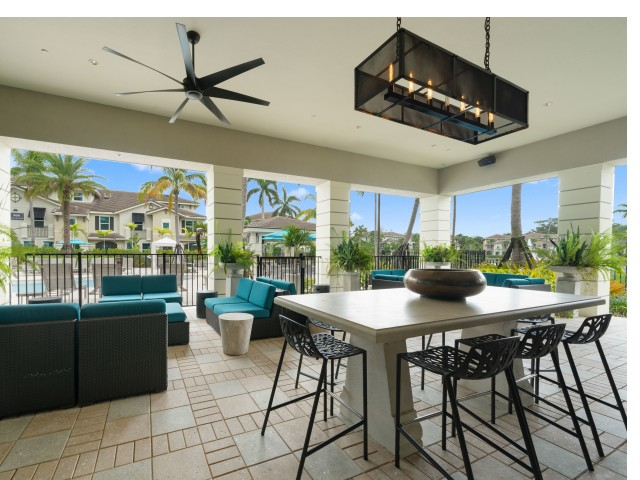 Covered open air poolside lounge with plush seating, dining table and ceiling fan
